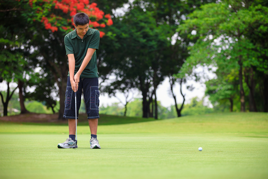 The Golf teenager boy player green putting