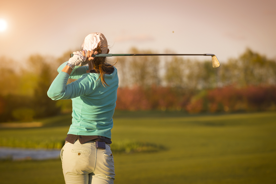 Close up of female golf player swinging golf club on fairway during sunset.