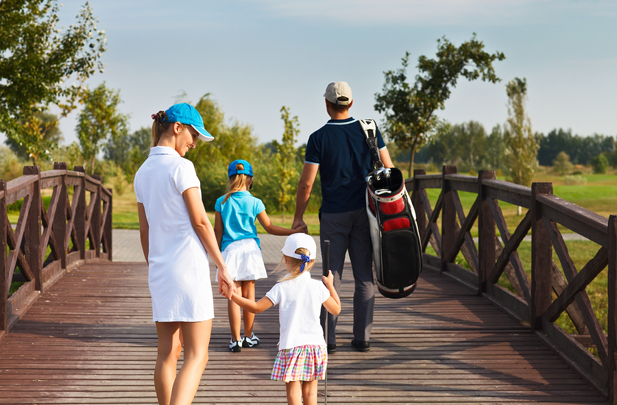 Family of golf players walking in the golf club