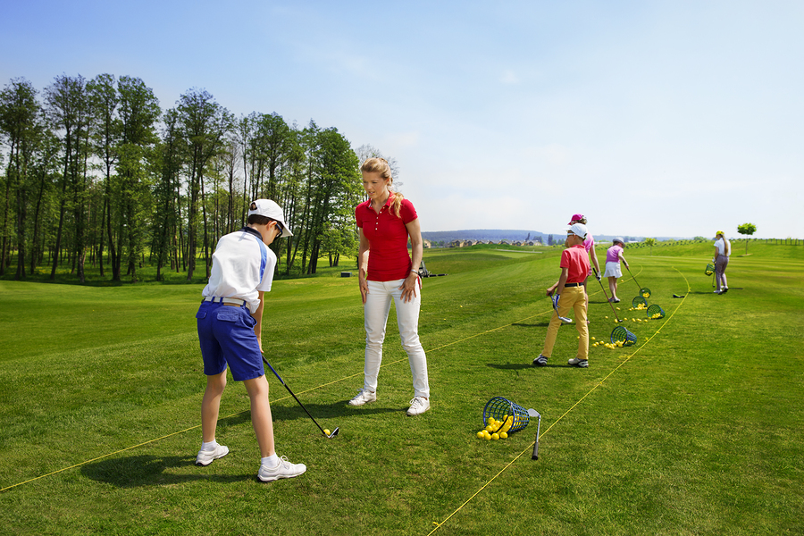 Kids practicing hits at golf school at summer day